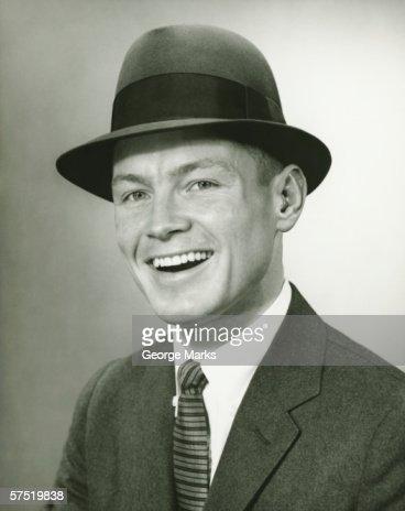 Smiling man in fedora hat posing un studio, (B&W), close-up, portrait