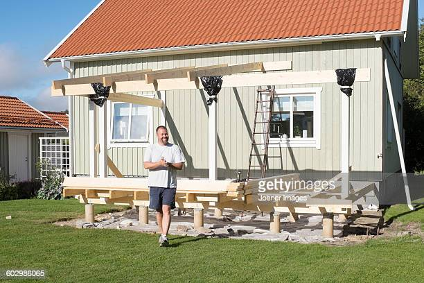 Smiling man in front of wooden house