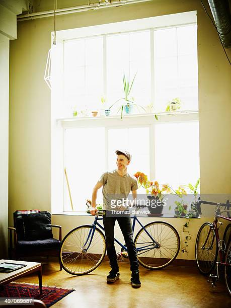 Smiling man in loft leaning against bike