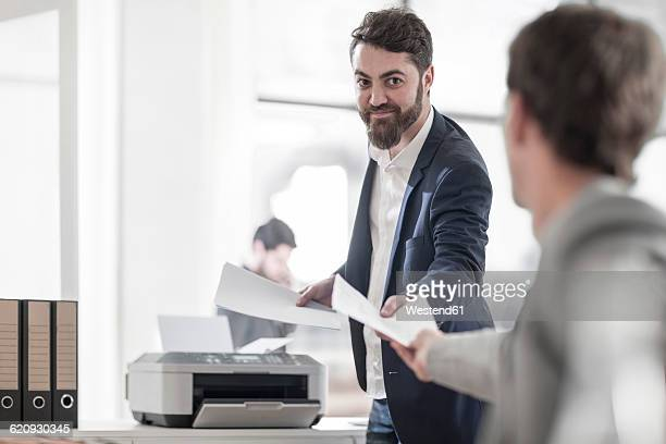 Smiling man in office handing over sheet to colleague