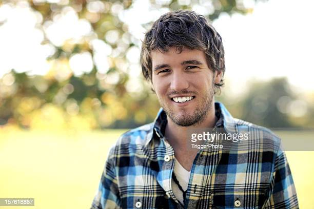 Smiling man in plaid shirt standing outdoors