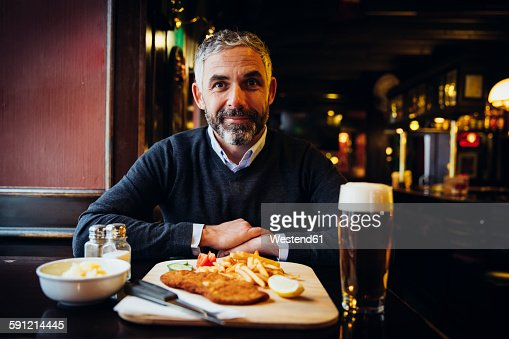 Smiling man in restaurant having Wiener Schnitzel with French fries