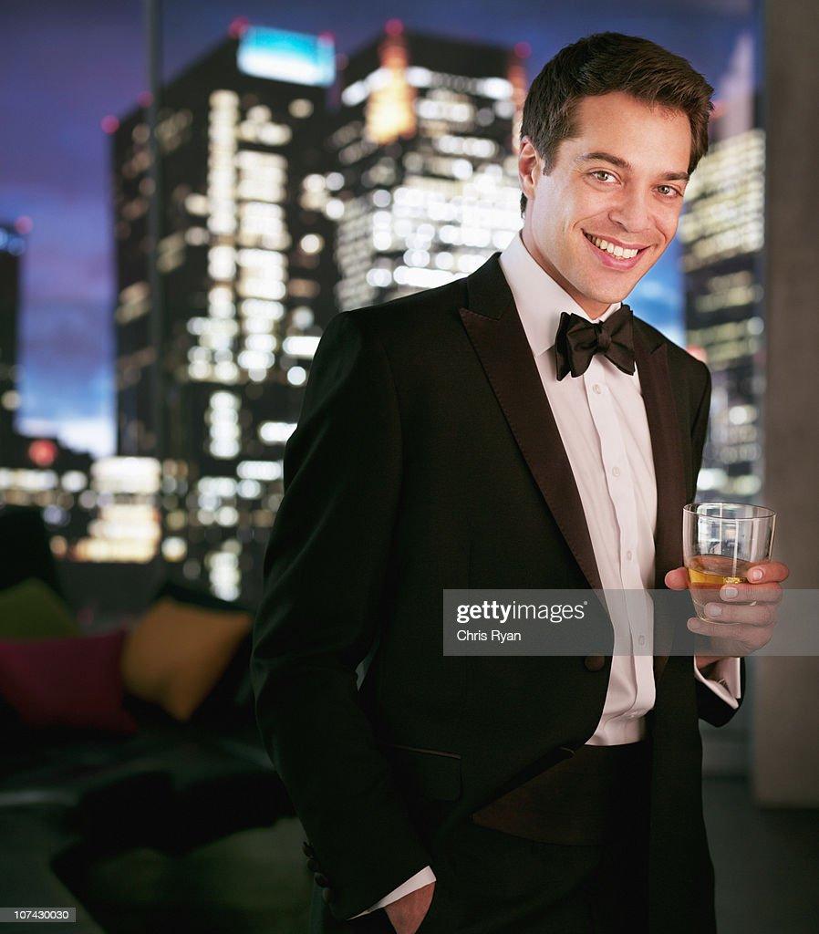 Smiling man in tuxedo drinking cocktail : Stock Photo