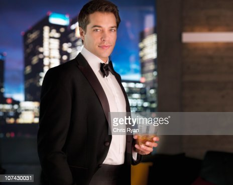 Smiling man in tuxedo drinking cocktail : Stock Photo