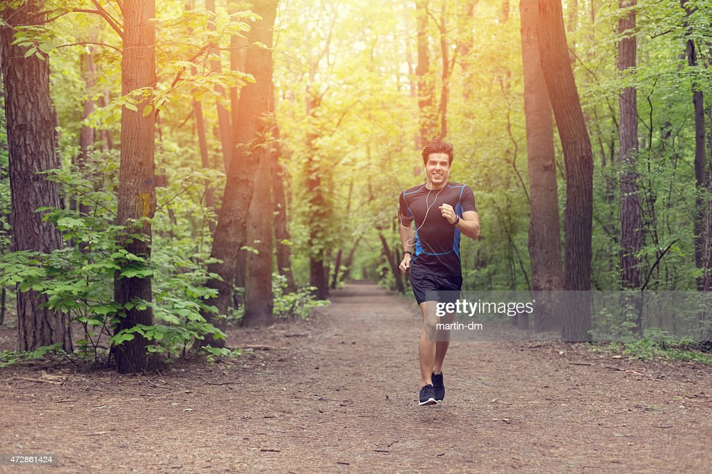 Sorridente uomo jogging nel parco : Foto stock
