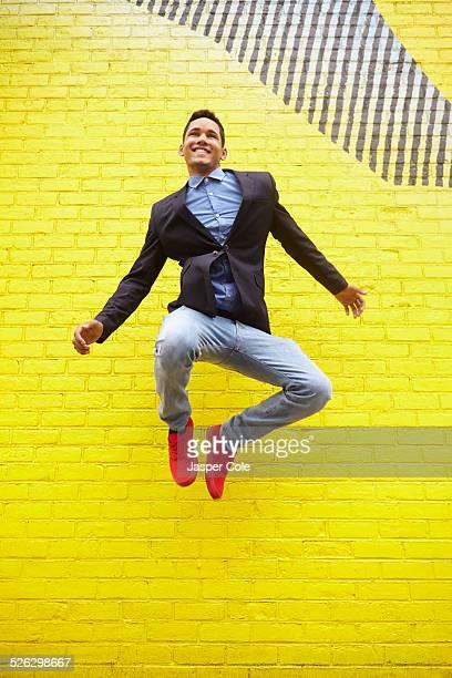 Smiling man jumping for joy near bright yellow wall