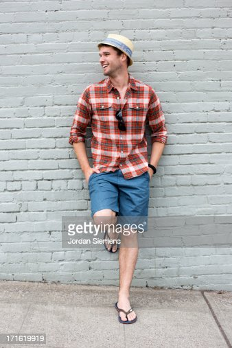A smiling man leaning agains a brick wall.