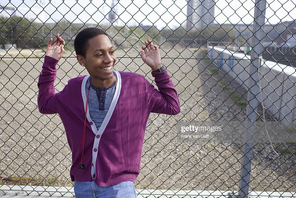 Smiling man leaning against fence : Stock Photo