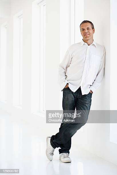 Smiling man leaning against wall
