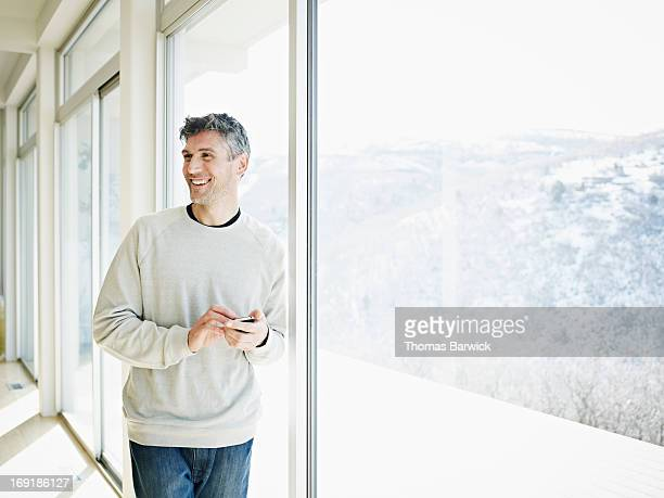 Smiling man leaning against window in home