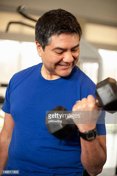 Smiling man lifting weights in gym