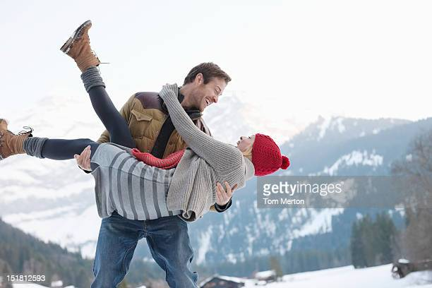 Smiling man lifting woman in snowy field