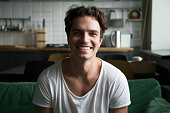 Smiling millennial man head shot portrait, happy handsome young blogger looking at camera sitting on kitchen sofa making video call or shooting blog, cheerful casual friendly guy posing at home