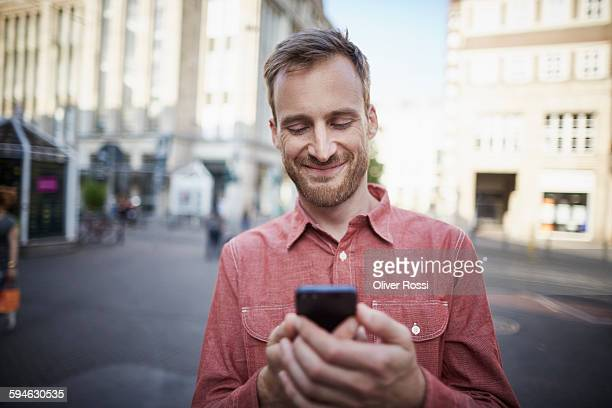Smiling man looking at cell phone outdoors
