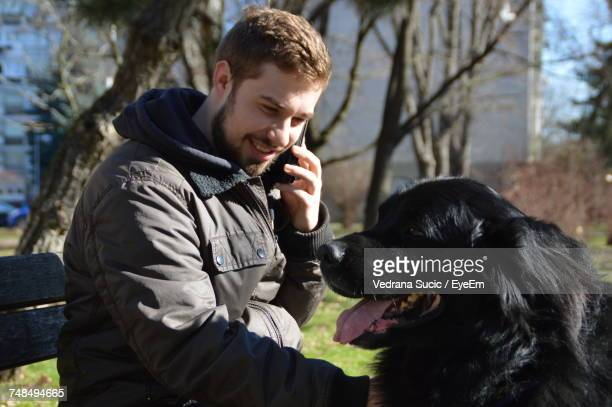 Smiling Man Looking At Dog While Talking On Phone