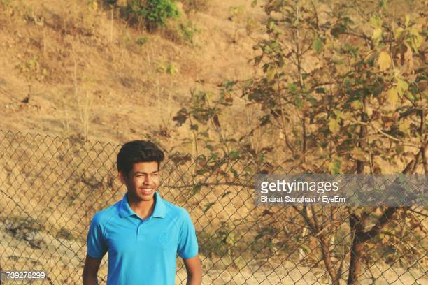 Smiling Man Looking Away While Standing By Fence