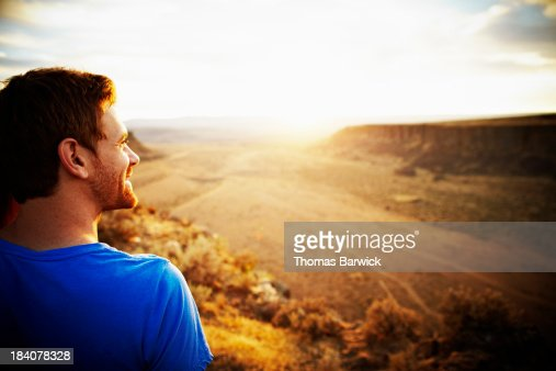 Smiling man looking out over canyon at sunset
