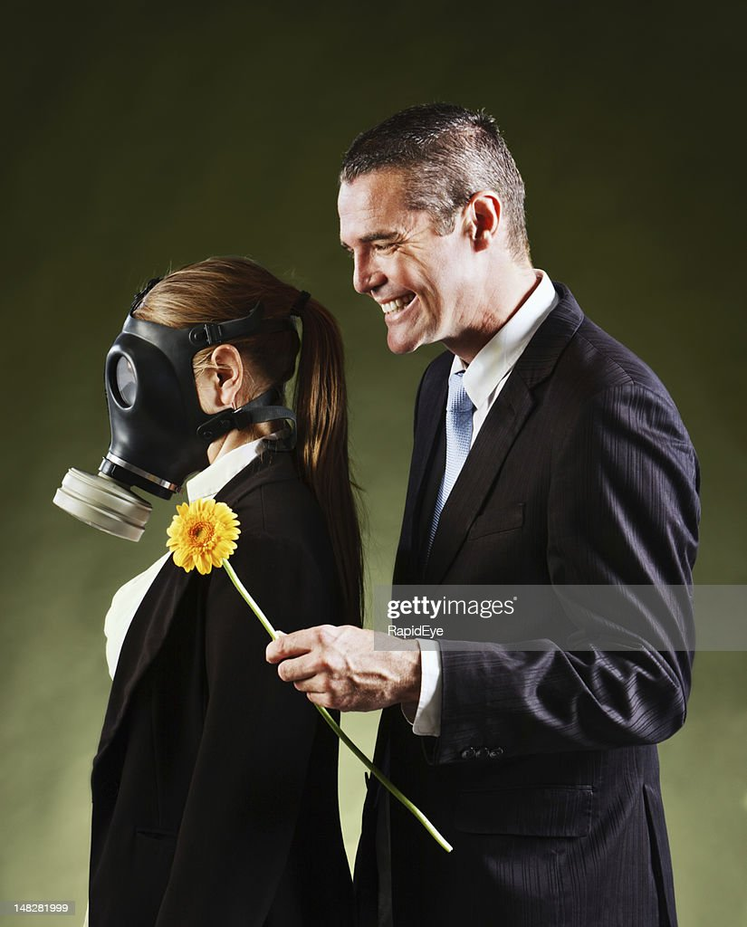 Smiling man offers woman in gas mask a flower : Stock Photo