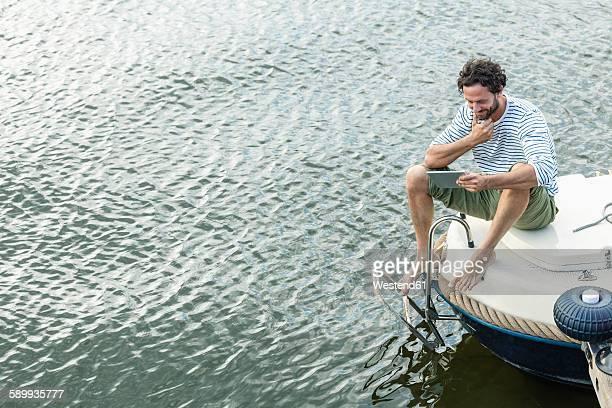 Smiling man on boat using digital tablet