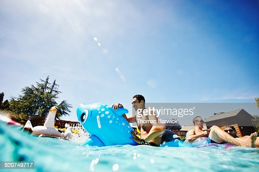 Smiling man on inflatable toy in outdoor pool
