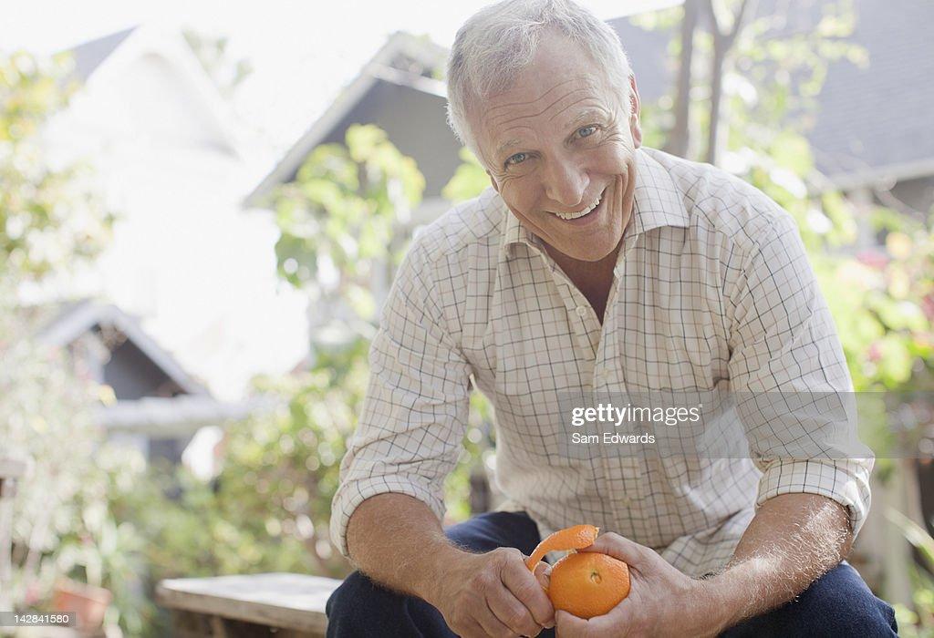 Smiling man peeling orange outdoors : Stock Photo