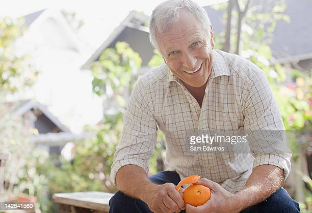 Smiling man peeling orange outdoors
