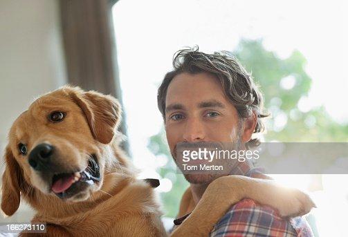 Smiling man petting dog indoors : Stock Photo