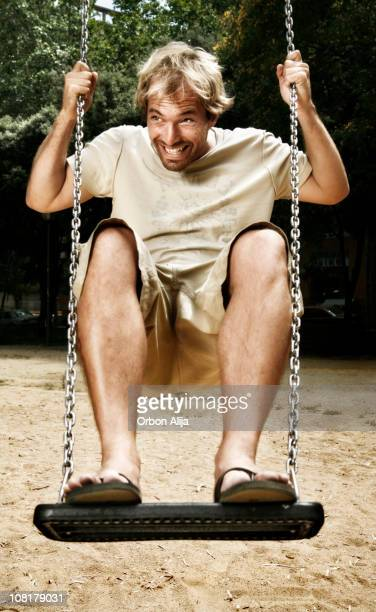 Smiling Man Playing and Standing on Swing at Playground