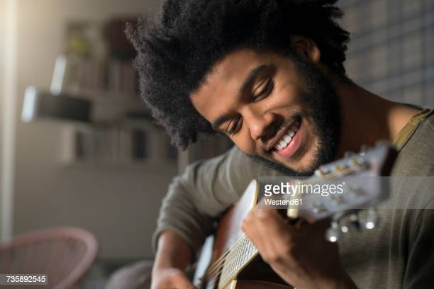 Smiling man playing guitar