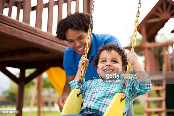 Smiling man playing on swing with son
