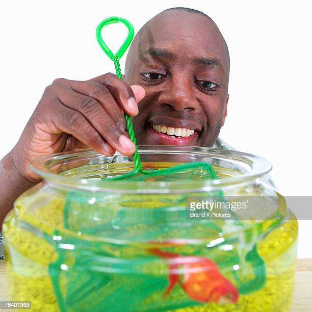 Smiling man playing with his goldfish