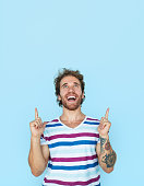 Handsome tattooed man smiling happily while pointing up on blue background.