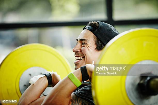 Smiling man preparing to press barbell over head