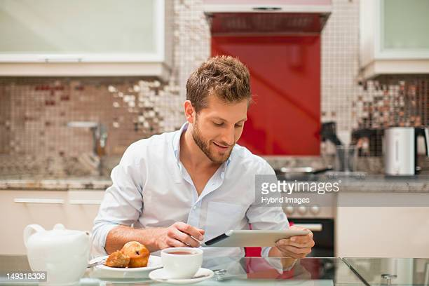 Smiling man reading at breakfast