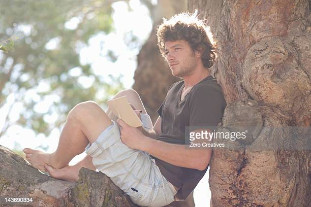 Homme souriant lecture dans tree
