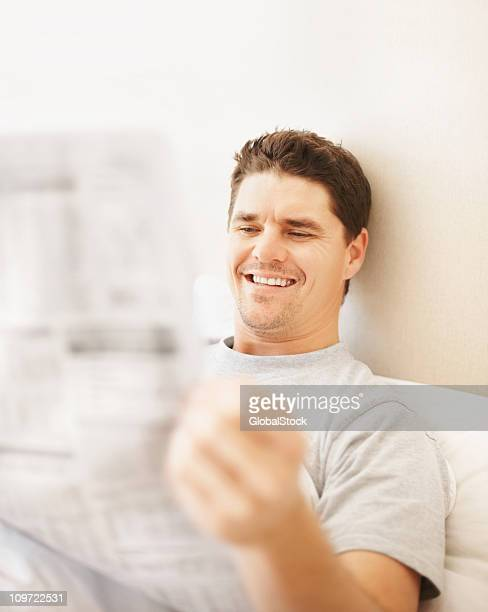 Smiling man reading newspaper in bed