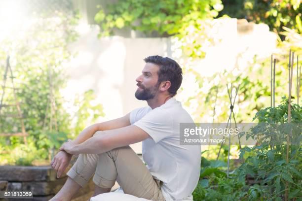 Smiling man relaxing in backyard