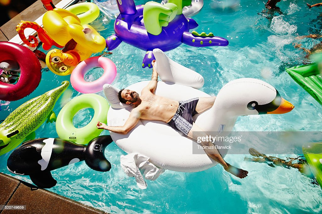 Smiling man relaxing on inflatable swan in pool : Stock Photo