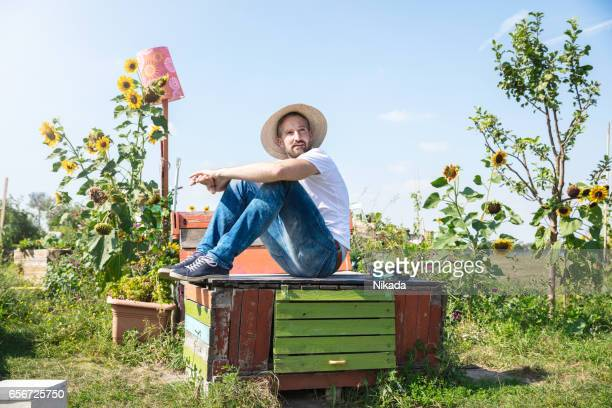 Smiling man resting on abandoned wooden table in garden