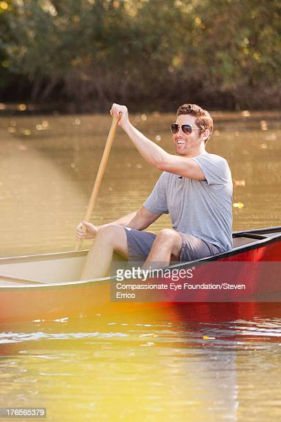Smiling man rowing canoe on river