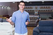 Smiling man seller showing prices in home furnishings store