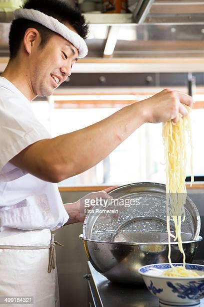 Smiling man serving ramen noodles in bowl
