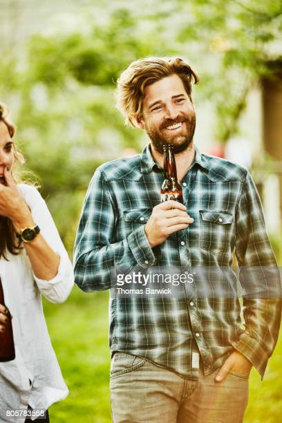 Smiling man sharing drinks with friends during backyard barbecue on summer evening