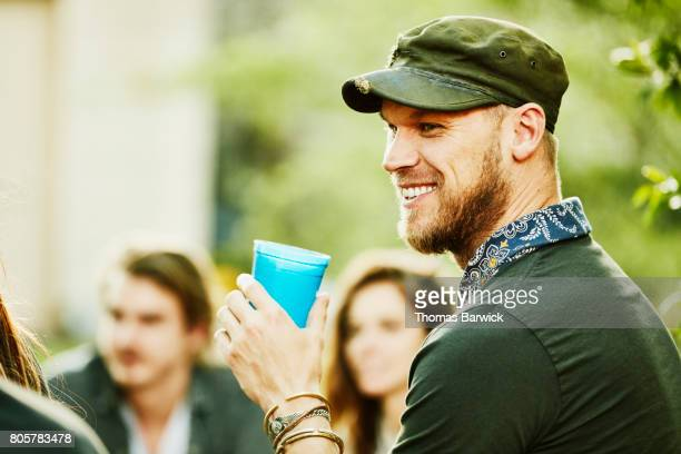 Smiling man sharing drinks with friends during backyard party on summer evening