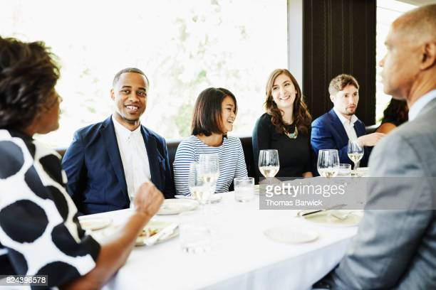 Smiling man sharing meal with parents and friends in restaurant