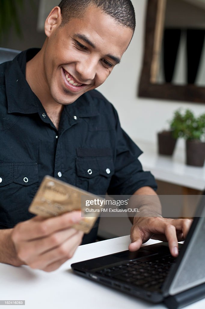 Smiling man shopping online : Stock Photo