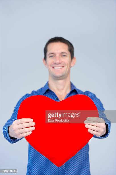 smiling man showing a big red heart