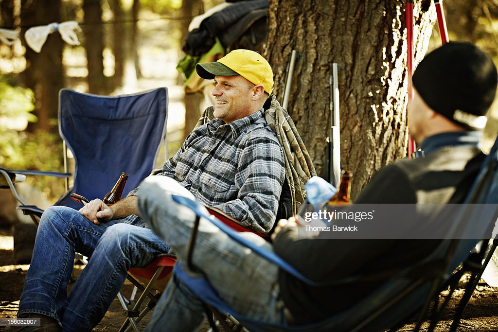 Smiling man sitting in hunting camp with friends : Stock Photo