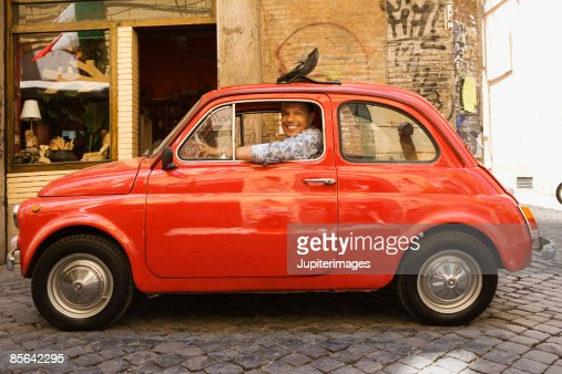 smiling man sitting in subcompact car stock photo getty images. Black Bedroom Furniture Sets. Home Design Ideas