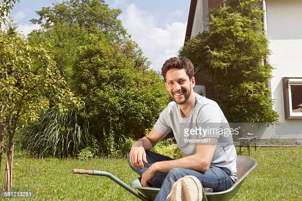 Smiling man sitting in wheelbarrow in garden